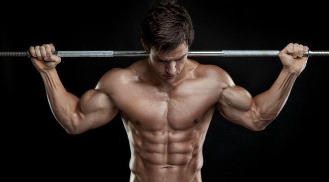 man with shredded abs holding bar
