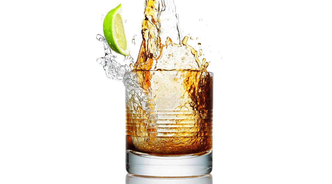 Cocktail splashing into a glass with lime
