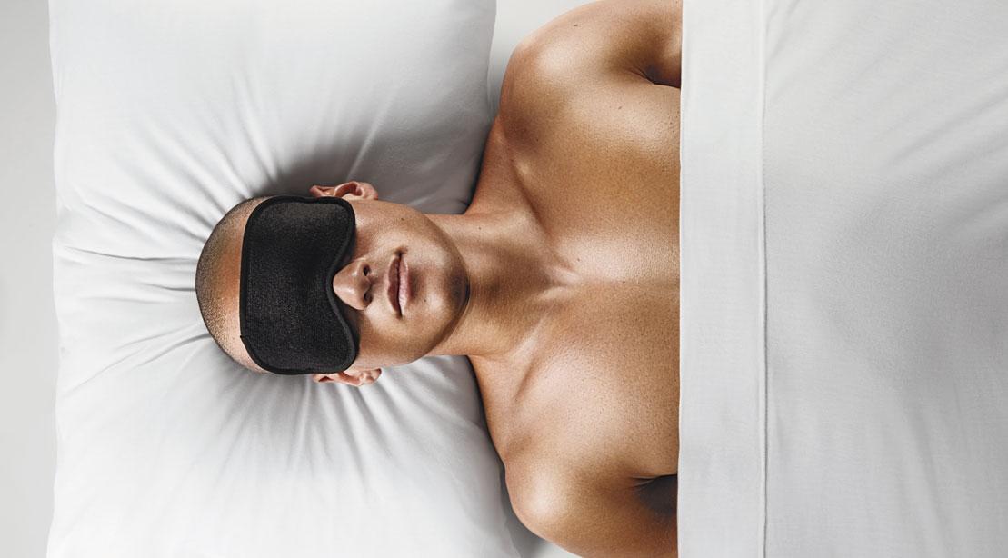 Man sleeping on white sheets with black eye mask