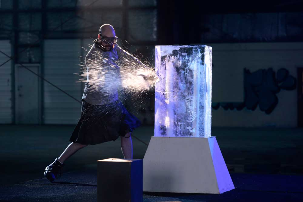 A contestant on 'Forged in Fire: Knife or Death' on History chops through an ice block.