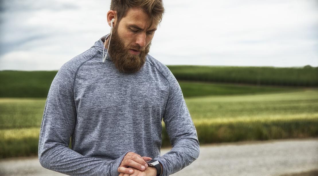 Man With Earphones Using Smartwatch, Standing Outdoors