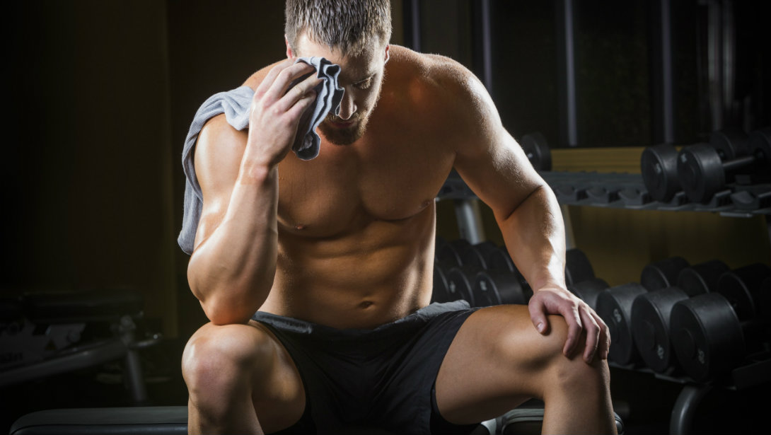 man resting on bench at gym