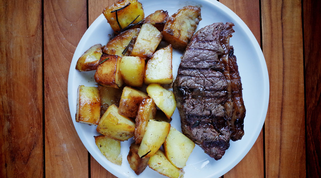 Steak With Potatoes Served In Plate On Table