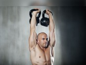 Man doing double kettlebell press thumbnail