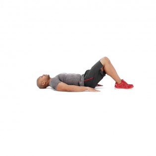 Lie On Your Back With Your Knees Together And Your Legs Bent To 90 Degrees,  Feet Planted On The Floor. Place Your Palms Face Down On The Floor For  Support.