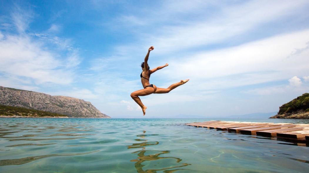 Woman Jumping Into Ocean thumbnail