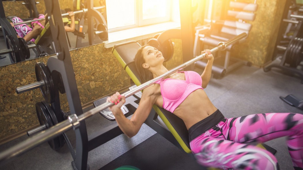 Woman doing incline barbell bench press wearing pink workout clothes thumbnail