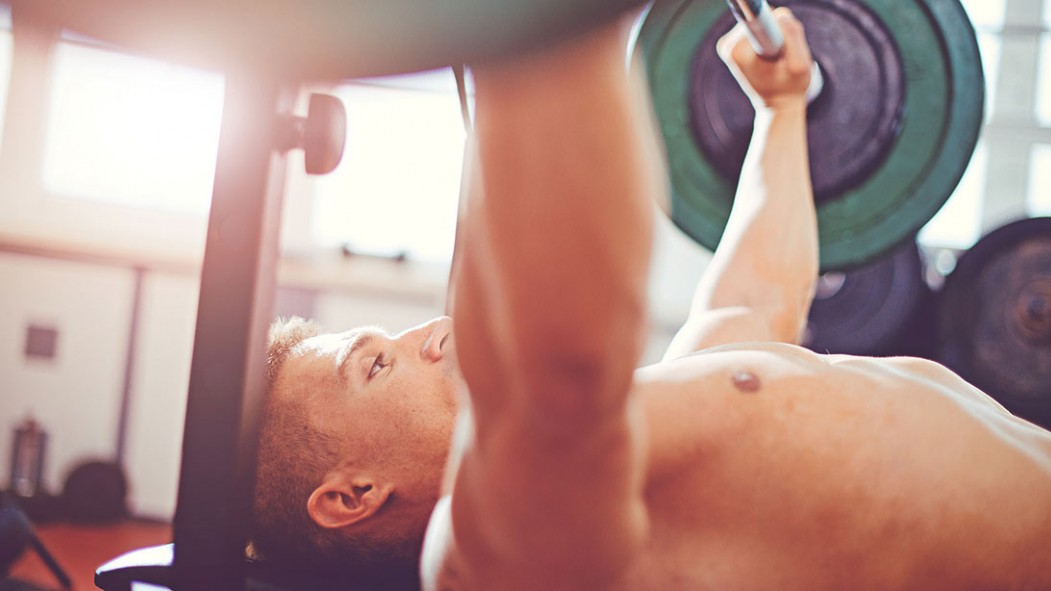 A man bench pressing in a gym thumbnail