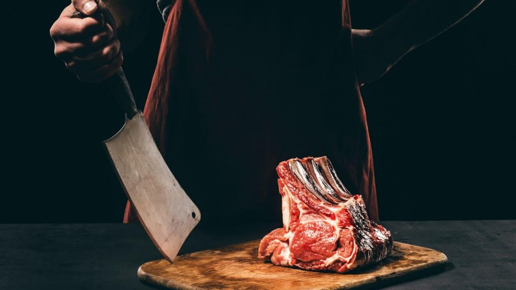Butcher-Standing-Behind-Steak-Cuts-Cleaver. thumbnail