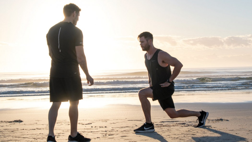 Chris-Hemsworth-Training-With-Luke-Zocchi-Lunges-On-Beach-Sunrise thumbnail