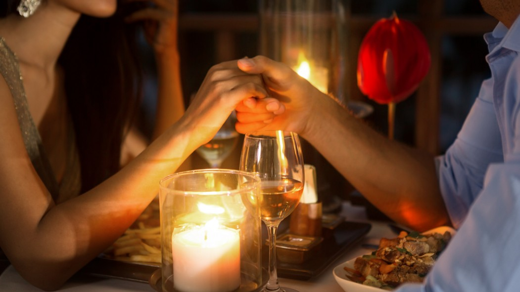 Couple-Holding-Hands-Over-Romantic-Dinner thumbnail