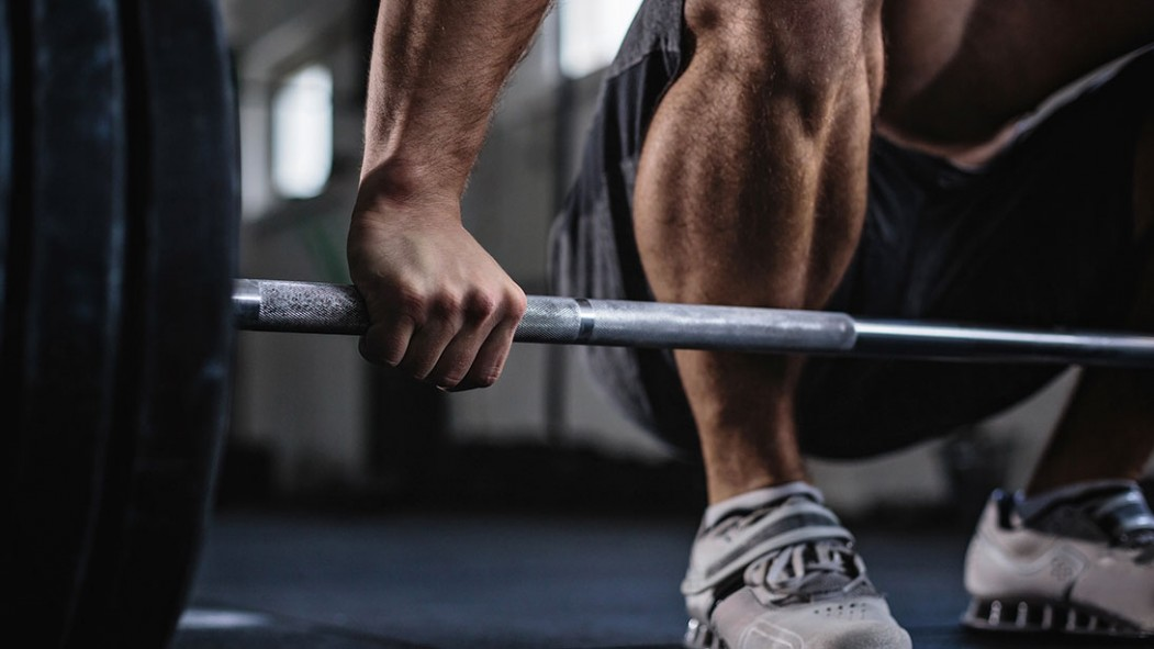 A picture of a person grabbing a barbell.  thumbnail