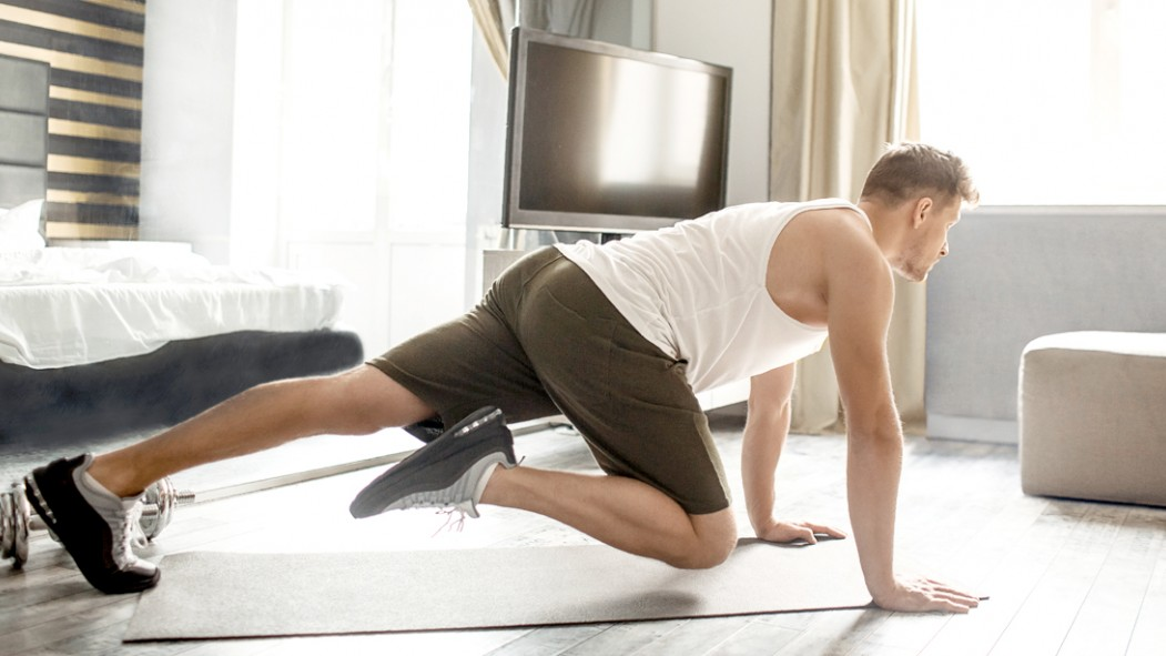 Man-Working-Out-At-Home-Bedroom-Performing-Mountain-Climber-Exercise thumbnail