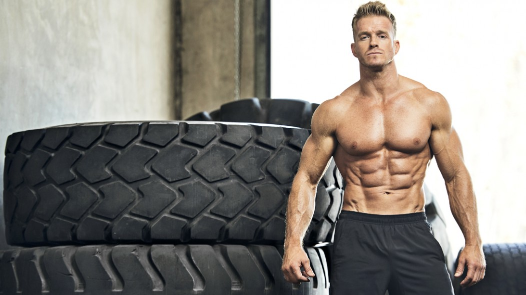 Muscular-Topless-Man-Standing-In-Front-Of-Tires thumbnail