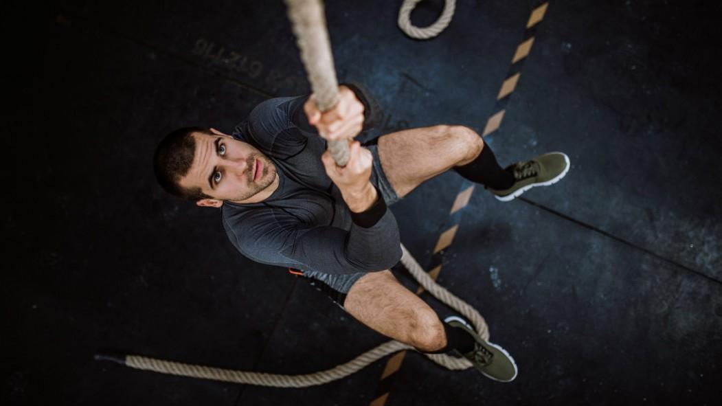 Man climbing rope at gym thumbnail