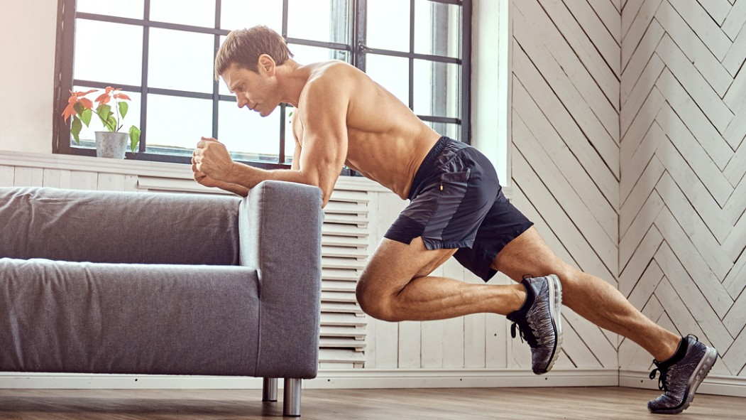Shirtless Man Exercising In Living Room Against A Couch thumbnail