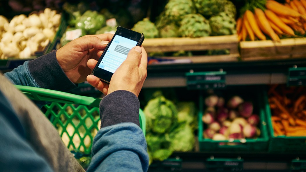Man shopping and using smartphone in supermarket thumbnail