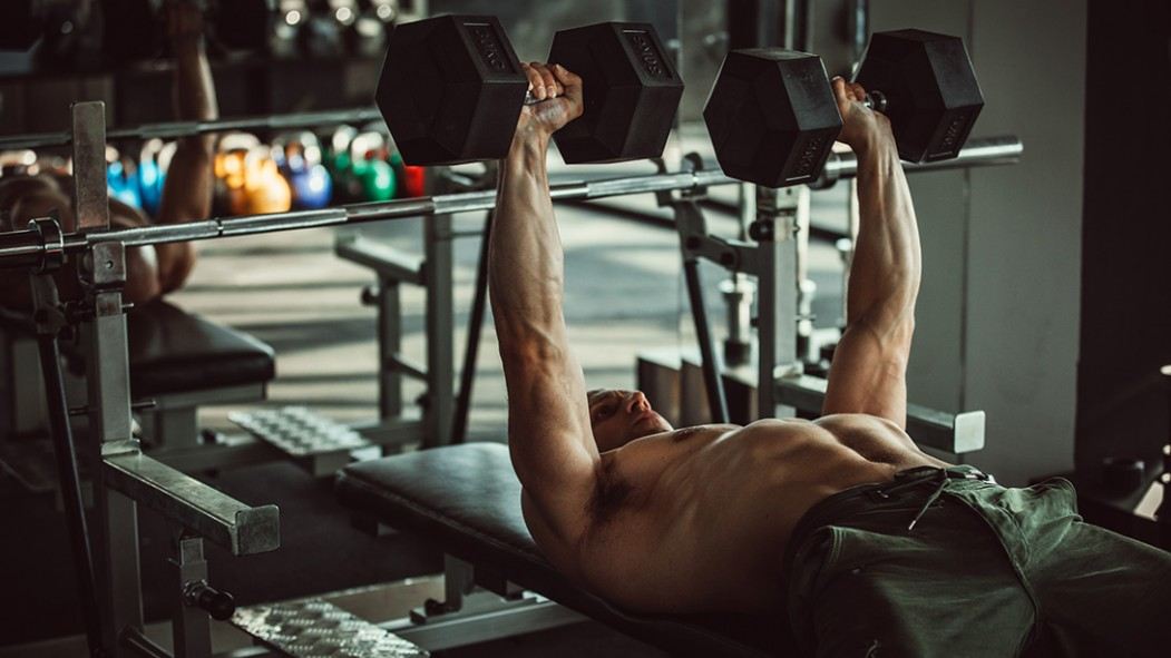 Young Man Exercising With Dumbbells in Gym thumbnail