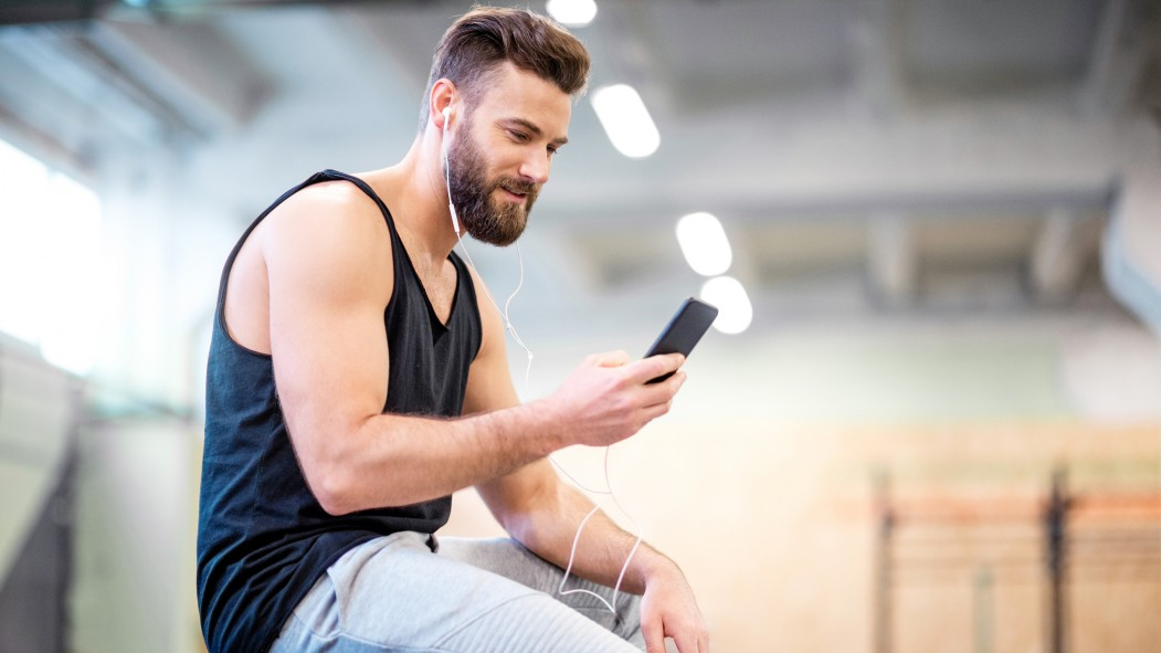 Man Looking at His Phone in the Gym thumbnail