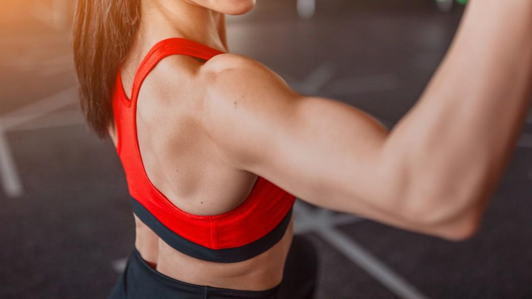Mujer entrenando hombros en el gimnasio miniatura