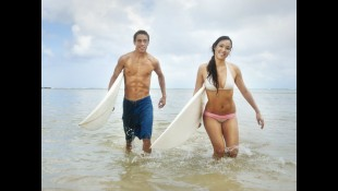 Couple carrying surfboards in the ocean thumbnail