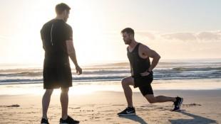Chris-Hemsworth-Training-With-Luke-Zocchi-Lunges-On-Beach-Sunrise thumbnail