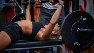 Woman lifting weights at gym thumbnail