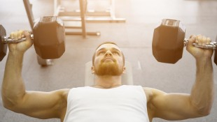 Young-Male-Focused-Performing-Lying-Dumbbell-Chest-Press miniatura