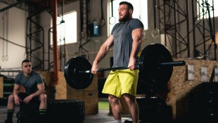 Man lifting heavy barbell at gym thumbnail