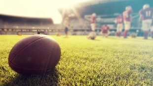 Close-Up Of Football Lying On Field Next To Football Players thumbnail