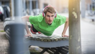 Young Sporty Man With Headphones Doing Pushups On Bench thumbnail