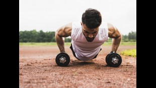 Man performing pushups on dumbbells thumbnail