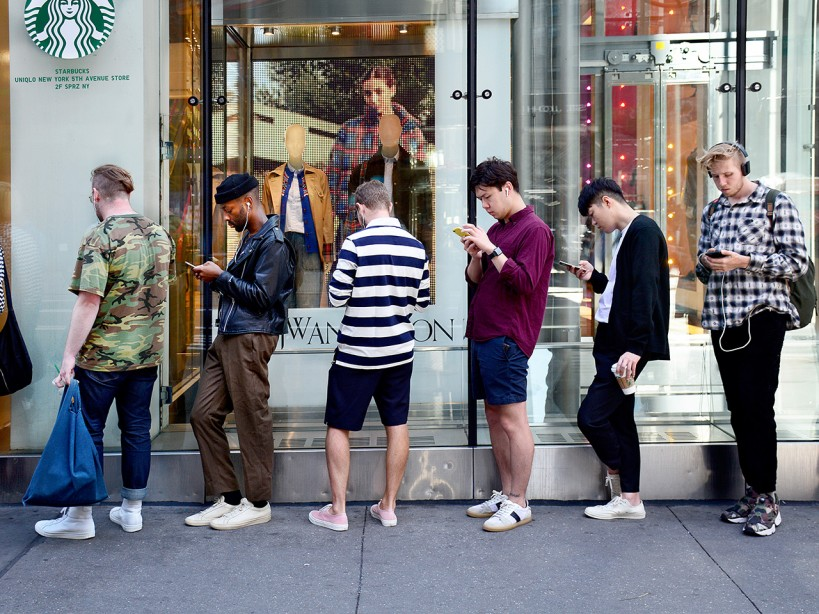 Men Using Smart Phones While Standing in Line