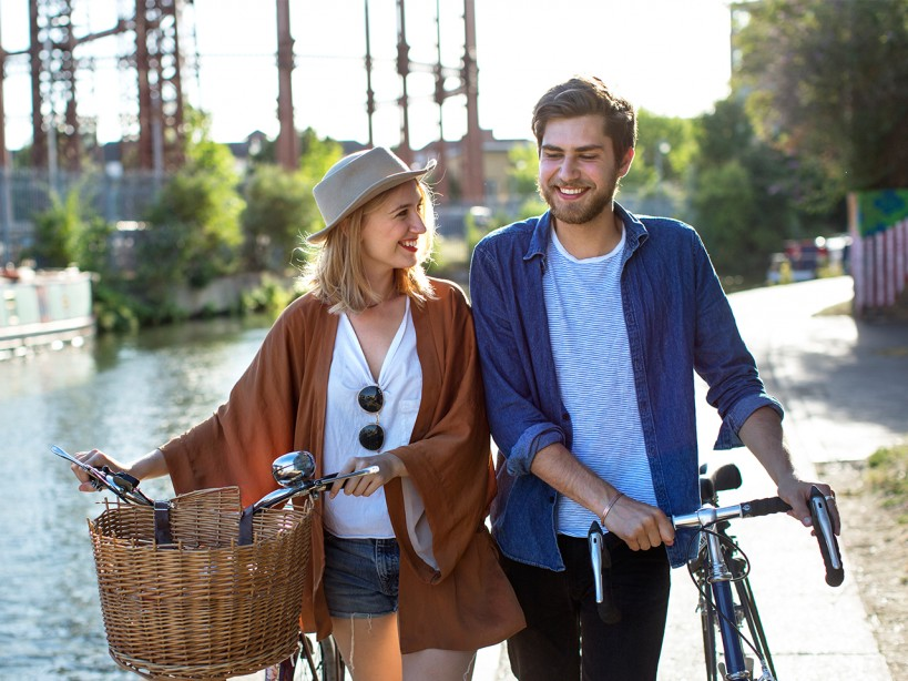 Couple Walking With Bikes Outside