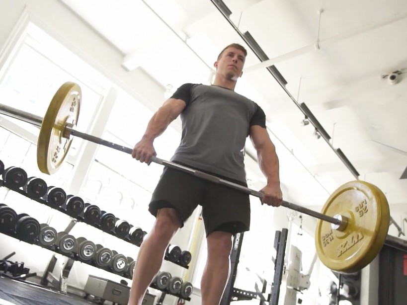 Man performs deadlift exercise