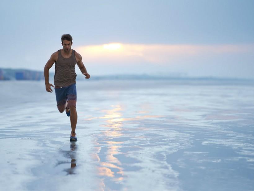 Man running along shore at beach