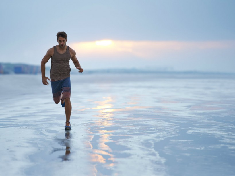 Man running along shore at beach