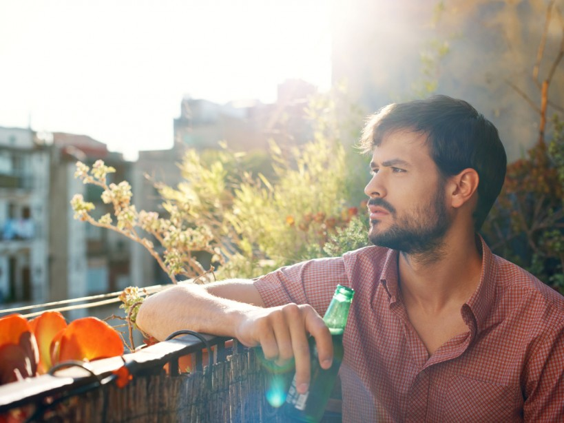 Man drinking beer on balcony