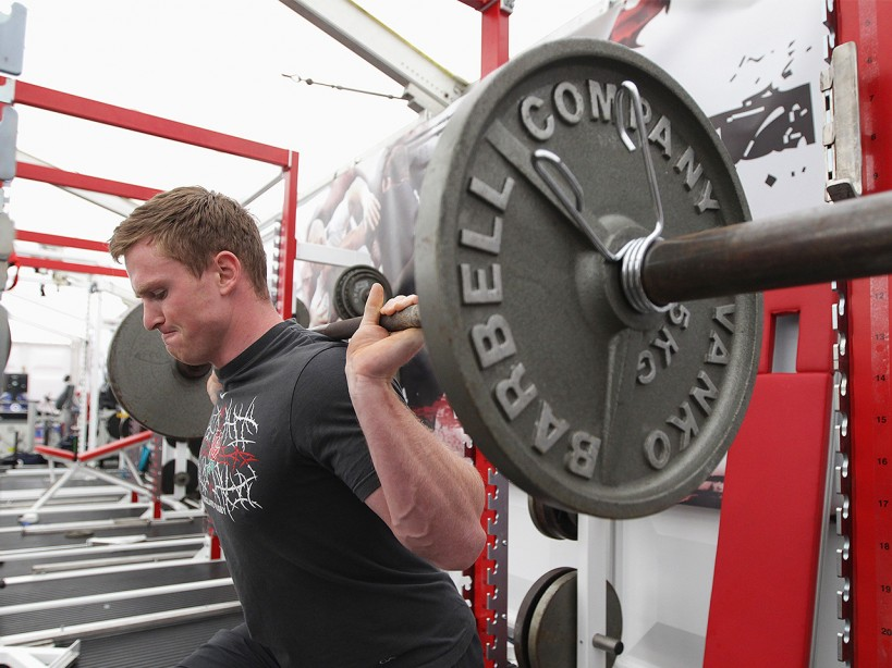 Man Lifts Barbell Weight During Training Session