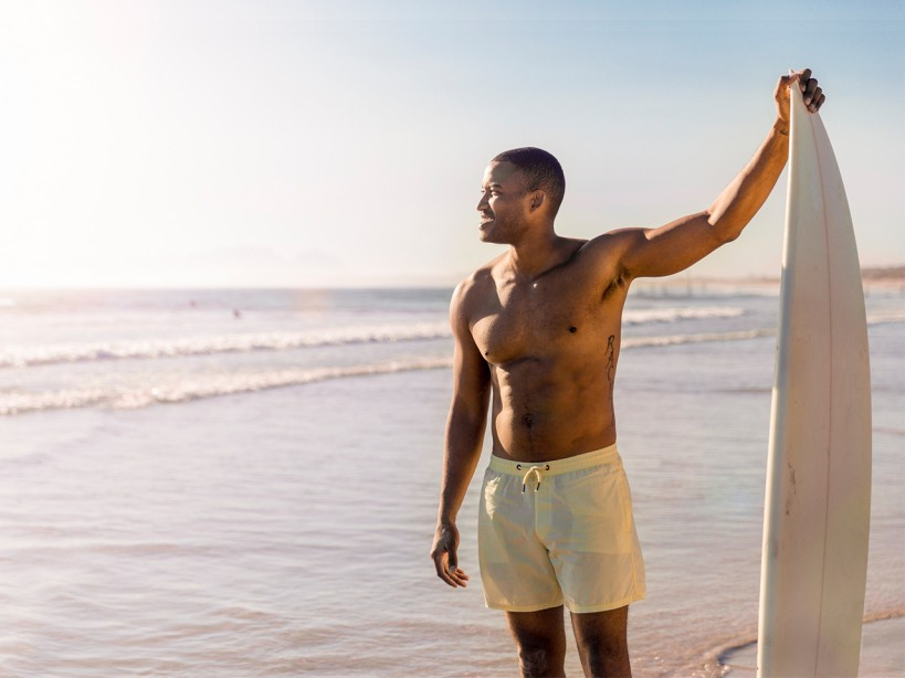 Shirtless Man At The Beach With Surfboard