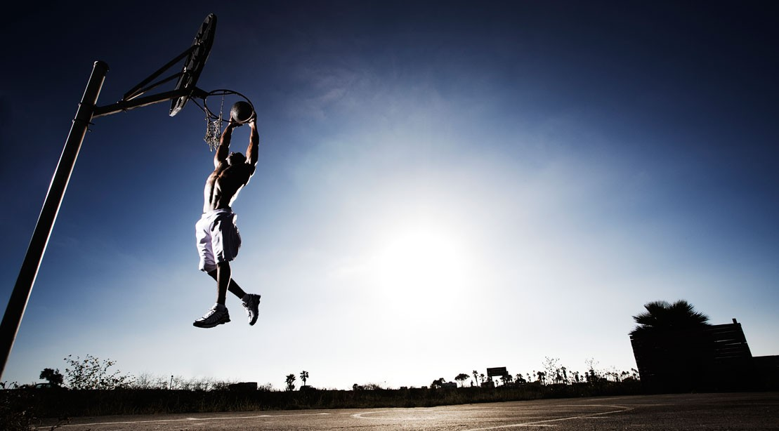 Man playing basketball, jumping and touching hoop