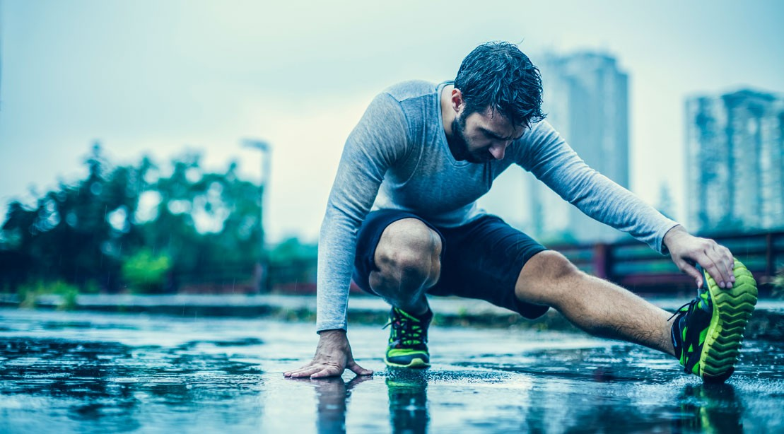 Man stretching legs on the ground in the rain