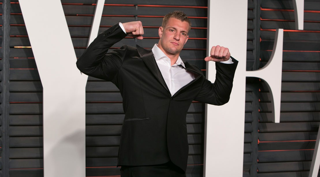Rob Gronkowski flexing his arms in a black suit