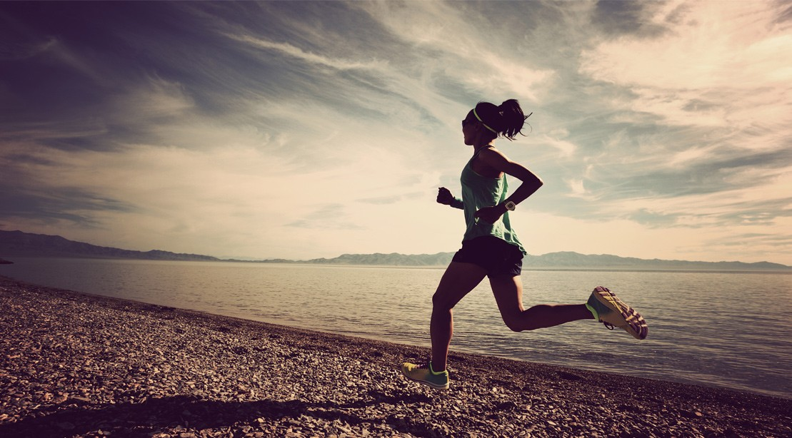 Woman running outdoors along the lake