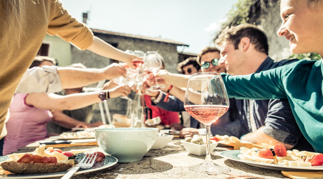 people drinking wine outside and toasting