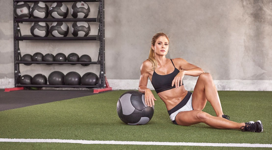 Torrie Wilson on the floor with a medicine ball