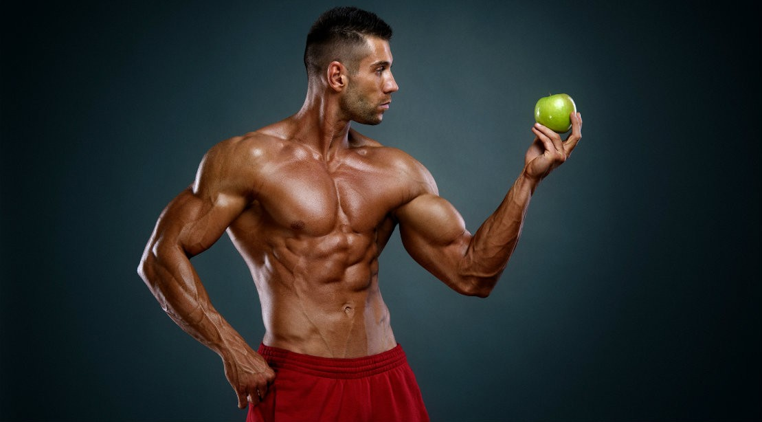 Bodybuilder holding apple