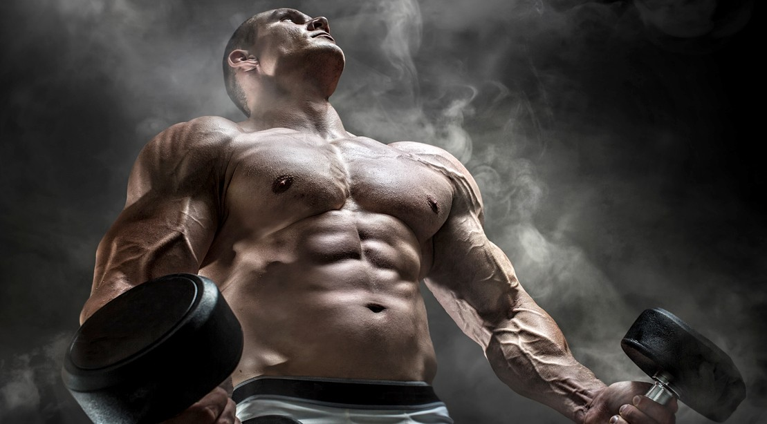 Bodybuilder-In-Smokey-Room-Looking-Up-Holding-Dumbbells