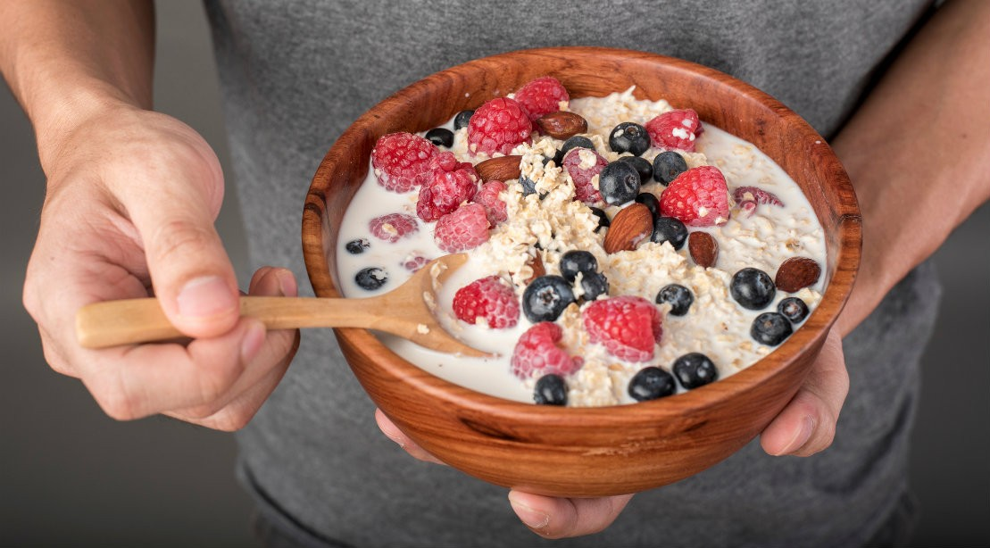 Man holding bowl of healthy oatmeal with added fruit