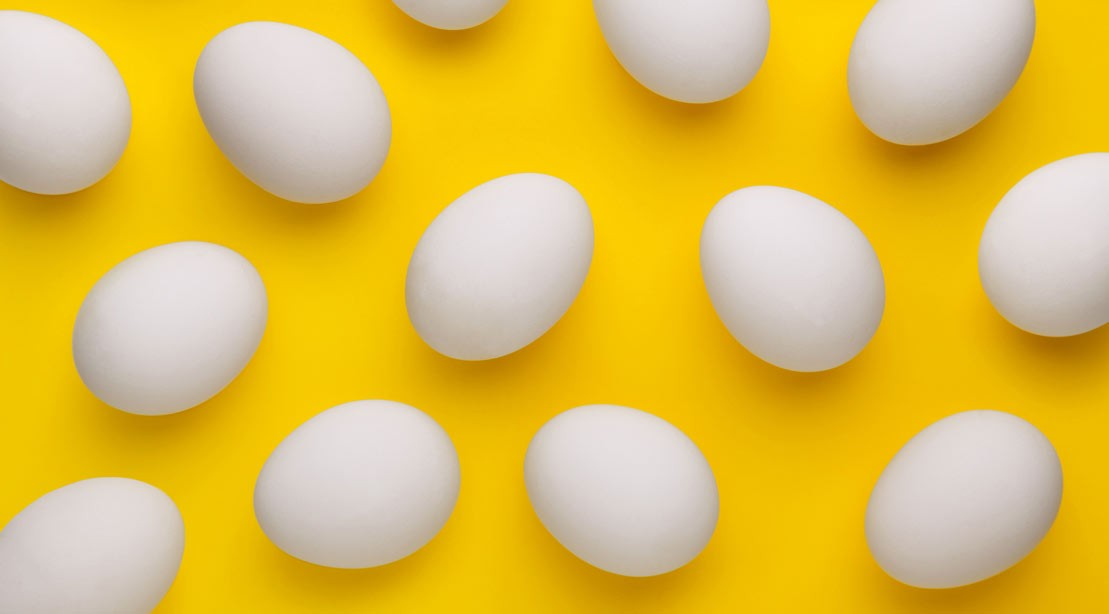 A photo of eggs against a yellow background.